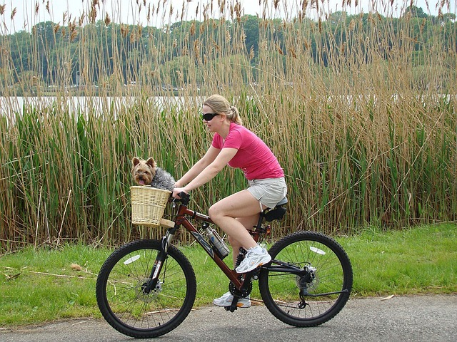 girl is cycling with a dog